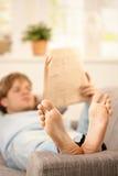 Equipe a leitura no sofá Foto de Stock Royalty Free