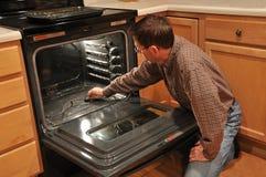 Equipe a limpeza de um forno Imagens de Stock Royalty Free