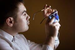 Equipe a limpeza de uma lente do homem de bem de vidros do computador fotografia de stock