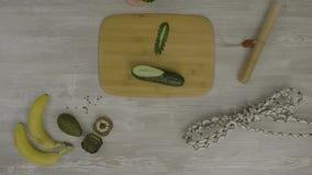 Equipe a mão do ` s na placa de madeira com uma faca que corta um pepino Na tabela são muitas tesouras, uma faca, vídeos de arquivo