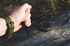 Equipe a mão do ` s que guarda a faca, compasso no início de uma sessão velho o forestSurvival na floresta, indo em férias à flor Imagem de Stock Royalty Free