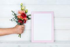 Equipe a mão do ` s que guarda flores e um quadro da foto no fundo de madeira Fotografia de Stock