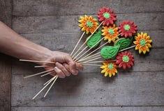 Equipe a mão do ` s que guarda um ramalhete de flores do pão-de-espécie no wo rústico Foto de Stock