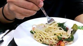 Equipe a mão do ` s que torce a forquilha e que toma comendo os espaguetes picantes no fundo do branco da tabela vídeos de arquivo