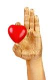 Equipe a mão dourada do ` s com um coração vermelho sobre o branco Fotografia de Stock Royalty Free