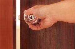 Equipe a mão que abre a porta, porta de madeira marrom com punho do metal imagens de stock