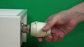 Equipe a mão que ajusta a temperatura do termostato do radiador no verde filme