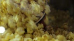 Equipe a mão que enche a cubeta plástica grande com o milho fritado pipoca do caramelo do queijo no cinema do cimena no fim gravo filme