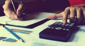Equipe a mão que faz a finança e calcule-a sobre o custo na tabela no hom fotografia de stock royalty free