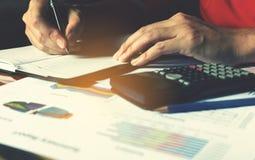 Equipe a mão que faz a finança e calcule-a sobre o custo na tabela no hom foto de stock royalty free