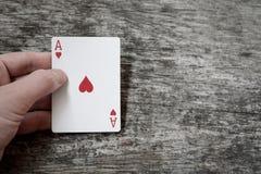 Equipe a mão que guarda o ás de cartão de jogo de corações com copyspace Fotografia de Stock