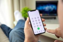 Equipe a mão que guarda o iPhone X com número de chamada na tela imagem de stock