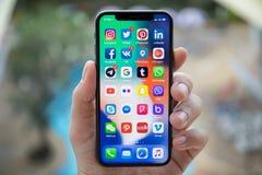Equipe a mão que guarda o iPhone X com rede social na tela Fotos de Stock Royalty Free