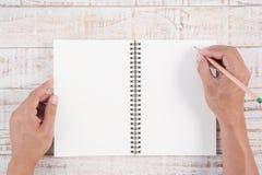 Equipe a mão que guarda o lápis e que escreve o caderno na tabela de madeira para Imagem de Stock Royalty Free