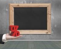 Equipe a mão que guarda o sinal de porcentagem vermelho com quadro-negro vazio Foto de Stock Royalty Free