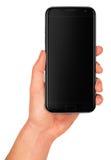 Equipe a mão que guarda o smartphone preto com tela vazia foto de stock royalty free