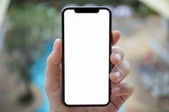 Equipe a mão que guarda o telefone com a associação isolada do fundo de tela Fotografia de Stock