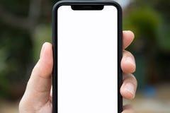 Equipe a mão que guarda o telefone com a tela isolada na natureza do fundo Fotografia de Stock Royalty Free