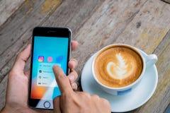 Equipe a mão que guarda o telefone esperto e que aponta na tela no café sh Imagens de Stock