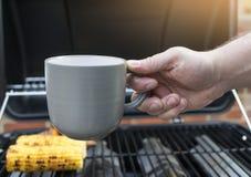 Equipe a mão que guarda a xícara de café com fundo obscuro do milho doce imagens de stock