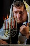 equipe a mão que leve velas na tabela do menorah servida para o Hanukkah fotos de stock