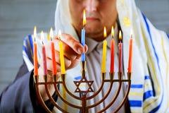 equipe a mão que leve velas na tabela do menorah servida para o Hanukkah fotografia de stock royalty free