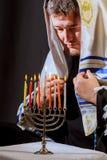 equipe a mão que leve velas no menorah na tabela servida para o hanukka imagem de stock