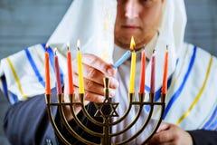 equipe a mão que leve velas no menorah na tabela servida para o Hanukkah fotografia de stock