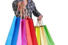 Equipe a mão que mantém sacos de compras coloridos isolados no fundo branco Fotografia de Stock