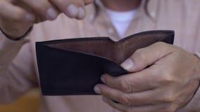 Equipe a mão que põe a moeda do centavo na carteira, economia do dinheiro, depósito bancário, fundo de pensão video estoque