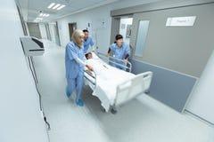 Equipe médica que empurra a cama da maca da emergência no corredor foto de stock