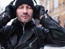 Equipe a música de escuta através dos fones de ouvido no stree de New York Inverno Fecha seus olhos Foto de Stock Royalty Free