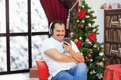 Equipe a música de escuta em fones de ouvido perto da árvore de Natal Fotos de Stock Royalty Free