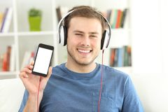 Equipe a música de escuta que mostra a tela esperta vazia do telefone fotos de stock royalty free