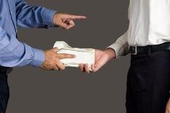Equipe a manipulação de um envelope completamente do dinheiro a uma outra pessoa com apontar do dedo Fotos de Stock Royalty Free