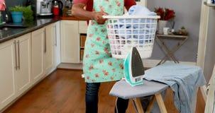 Equipe manter a cubeta completa da roupa na cozinha 4k video estoque