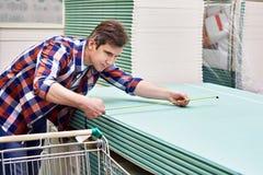 Equipe medidas com as folhas do drywall da roleta no companheiro da construção de loja foto de stock
