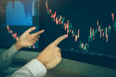 Equipe mercado de valores de a??o de executivos de troca do gr?fico apontando e da an?lise do agente no tela de computador no esc imagens de stock royalty free