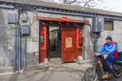 Equipe a montada de um motorcyle em um hutong no Pequim imagem de stock