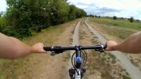 Equipe a montada de uma bicicleta em um campo em uma grama verde vídeos de arquivo