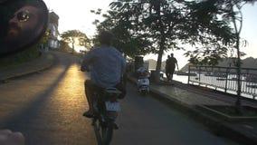 Equipe a montada de uma bicicleta motorizada ao longo da baía longa do Ha video estoque