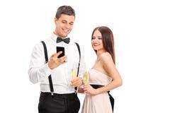 Equipe mostrar algo em seu telefone celular a uma mulher Fotos de Stock Royalty Free