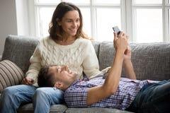 Equipe mostrar a mulher o telefone celular novo app que relaxa no sofá fotos de stock