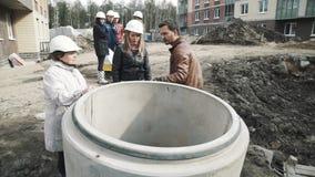 Equipe mostrar mulheres nos capacetes de segurança sobre o anel concreto da câmara de visita no terreno de construção filme
