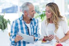 Equipe mostrar a tabuleta digital à mulher no restaurante imagens de stock