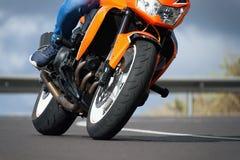 Equipe a motocicleta da equitação na curva da estrada asfaltada com rural Fotografia de Stock