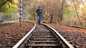 Equipe movimentar-se na estrada de ferro da trilha em Autumn Season na floresta vídeos de arquivo