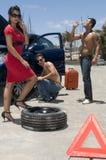 Equipe a mudança de uma roda de uma mulher bonita Fotografia de Stock Royalty Free
