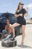Equipe a mudança de uma roda para ajudar uma mulher Imagem de Stock