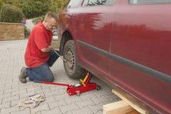 Equipe a mudança do pneumático puncionado em seu carro que afrouxa as porcas com uma chave inglesa da roda antes de levantar acim imagens de stock